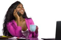 Молодой кофе счастливой и привлекательной задней афро американской бизнес-леди выпивая ослабил работающ дома стол офиса говоря на стоковые фото