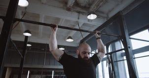 Молодой красавчик-кавказец, который делает подтягивания, прыгает в покой во время экстремальных тренировок в тренажерном зале, за сток-видео