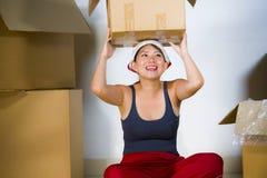 Молодой красивой и счастливой азиатской корейской возбужденный женщиной дома пол живя комнаты распаковывая пожитки от картонных к стоковое изображение