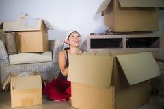 Молодой красивой и счастливой азиатской корейской возбужденный женщиной дома пол живя комнаты распаковывая пожитки от картонных к стоковое фото