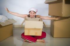 Молодой красивой и счастливой азиатской корейской возбужденный женщиной дома пол живя комнаты распаковывая пожитки от картонных к стоковая фотография