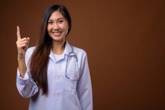 Молодой красивый азиатский доктор женщины против коричневой предпосылки стоковые изображения
