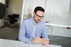 Молодой красивый архитектор работая на компьтер-книжке в офисе Стоковое Изображение