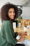 Молодой красивый африканский студент девушки смотря камеру сидя в кофе кафа усмехаясь выпивая Стоковое фото RF