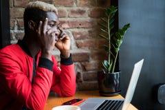 Молодой красивый Афро-американский человек используя компьтер-книжку и думающ пока работающ в кафе стоковые изображения