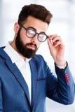 Молодой красивый бизнесмен представляя на рабочем месте стоковая фотография rf