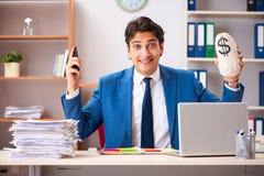 Молодой красивый бизнесмен работая в офисе стоковое изображение rf