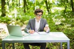 Молодой красивый бизнесмен работая на компьтер-книжке на телефоне пользы таблицы офиса и отправляя СМС в зеленом парке владение д стоковая фотография