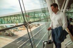 Молодой красивый бизнесмен стоит с чемоданом около окна в аэропорте, ж стоковые фотографии rf