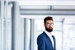 Молодой красивый бизнесмен стоя на ` s компании крытом стоковая фотография