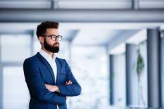 Молодой красивый бизнесмен стоя на ` s компании крытом стоковая фотография rf