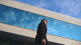 Молодой красивый бизнесмен с идти портфеля внешний вдоль современного офисного здания Бизнесмен в sunglass акции видеоматериалы