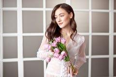 Молодой красивый букет весны удерживания девушки брюнета тюльпанов в ее руках стоковая фотография