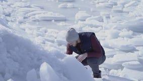 Молодой красивый геолог человека искал что-то в леднике холодного льда идя снег за морем зимы ( акции видеоматериалы