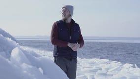 Молодой красивый геолог человека сфокусированный на что-то около ледника холодного льда идя снег за морем зимы ( акции видеоматериалы