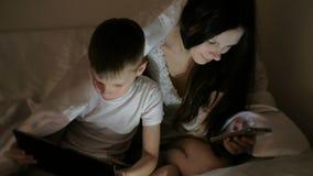Молодой красивый интернет просматривать мамы женщины в ее телефоне пока ее шарж сына наблюдая на таблетке акции видеоматериалы