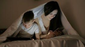 Молодой красивый интернет просматривать мамы женщины в ее телефоне пока ее шарж сына наблюдая на таблетке сток-видео