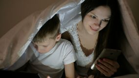 Молодой красивый интернет просматривать мамы женщины в ее телефоне пока ее шарж сына наблюдая на таблетке видеоматериал