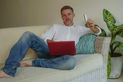 Молодой красивый и привлекательный счастливый человек делая покупки интернета онлайн с усмехаться кресла софы кредитной карточки  стоковое фото