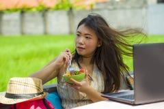 Молодой красивый и счастливый азиатский цифровой кочевник или китайская туристская сеть девушки outdoors при портативный компьюте Стоковые Фото