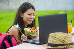Молодой красивый и счастливый азиатский цифровой кочевник или китайская туристская сеть девушки outdoors при портативный компьюте Стоковое фото RF