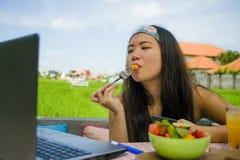 Молодой красивый и счастливый азиатский цифровой кочевник или китайская туристская сеть девушки outdoors при портативный компьюте Стоковое Изображение RF