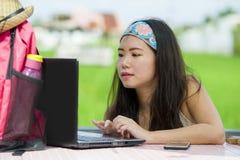 Молодой красивый и счастливый азиатский цифровой кочевник или корейская туристская сеть девушки outdoors с портативным компьютеро Стоковое Изображение