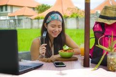 Молодой красивый и счастливый азиатский цифровой кочевник или китайская туристская сеть девушки outdoors при портативный компьюте Стоковая Фотография RF