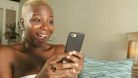 молодой красивый и счастливый черный Афро-американский усмехаться женщины возбужденный используя средства массовой информации app стоковое фото