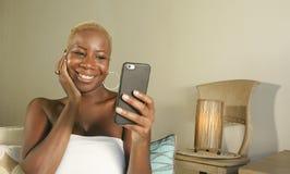 молодой красивый и счастливый черный Афро-американский усмехаться женщины возбужденный используя средства массовой информации app стоковое фото rf