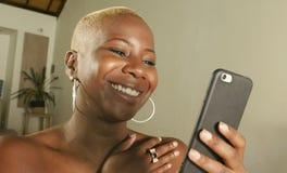 молодой красивый и счастливый черный Афро-американский усмехаться женщины возбужденный используя средства массовой информации app стоковая фотография