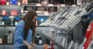 Молодой красивый сексуальный брюнет выбирает blender для кухни в магазине приборов сток-видео