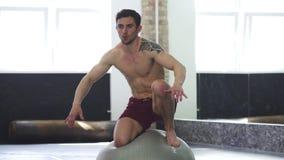 Молодой красивый сорванный мужской спортсмен балансируя на шарике фитнеса видеоматериал