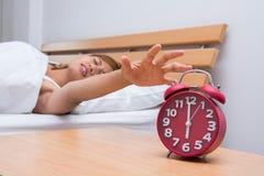 Молодой красивый спать и будильник женщины в спальне на hom Стоковые Изображения RF