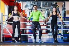 Молодой красивый тренер с молодой и sporty женщиной в спортзале изолированная принципиальной схемой белизна спорта стоковое изображение rf