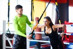 Молодой красивый тренер с красивой женщиной в спортзале Концепция спорт стоковая фотография rf