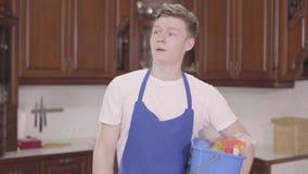 Молодой красивый уставший человек, берущий корзину с моющими средствами и протирающий руку лбом День очистки сток-видео