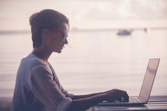 Молодой красивый фрилансер путешественника хиппи женщины с компьтер-книжкой на t Стоковые Изображения RF