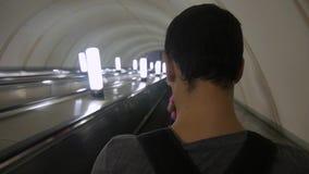 Молодой красивый человек битника путешествует на эскалаторе в метро Снятый от задней части После молодого человека по мере того к акции видеоматериалы