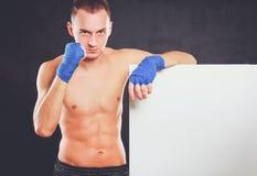 Молодой красивый человек боксера стоя близко доска, изолированная на черной предпосылке Стоковое Фото