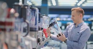 Молодой красивый человек в магазине приборов выбирает blender для его кухни смотря и держа различные модели в его руках сток-видео
