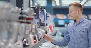 Молодой красивый человек в магазине приборов выбирает blender для его кухни акции видеоматериалы