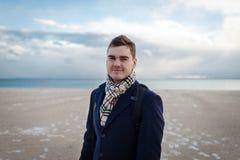 Молодой красивый человек в элегантных одеждах на пляже зимы в NYC Стоковые Фотографии RF