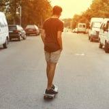Молодой красивый человек ехать скейтборд вниз по улице на заходе солнца Американские перемещения парня вокруг города летом стоковые изображения rf