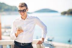 Молодой красивый человек наслаждаясь пребыванием на роскошном курортном отеле с панорамным взглядом на море Стоковое фото RF
