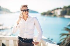 Молодой красивый человек наслаждаясь пребыванием на роскошном курортном отеле с панорамным взглядом на море Стоковая Фотография
