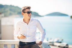 Молодой красивый человек наслаждаясь пребыванием на роскошном курортном отеле с панорамным взглядом на море Стоковое Изображение