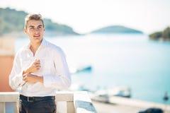 Молодой красивый человек наслаждаясь пребыванием на роскошном курортном отеле с панорамным взглядом на море Стоковая Фотография RF