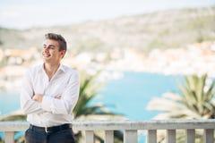 Молодой красивый человек наслаждаясь пребыванием на роскошном курортном отеле с панорамным взглядом на море Стоковое Изображение RF