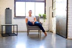 Молодой красивый человек ослабляя в кресле в стиле apar просторной квартиры стоковое фото rf